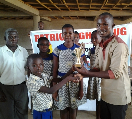 National Coordinator Eric Opoku Agyemang presents trophy to SDA school